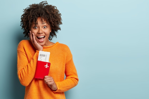 Jonge vrouw met afro kapsel oranje trui dragen