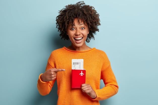 Jonge vrouw met afro-kapsel oranje trui dragen