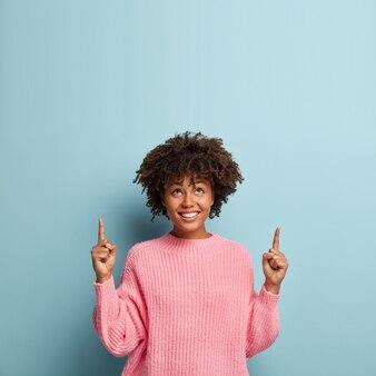Jonge vrouw met afro kapsel roze trui dragen