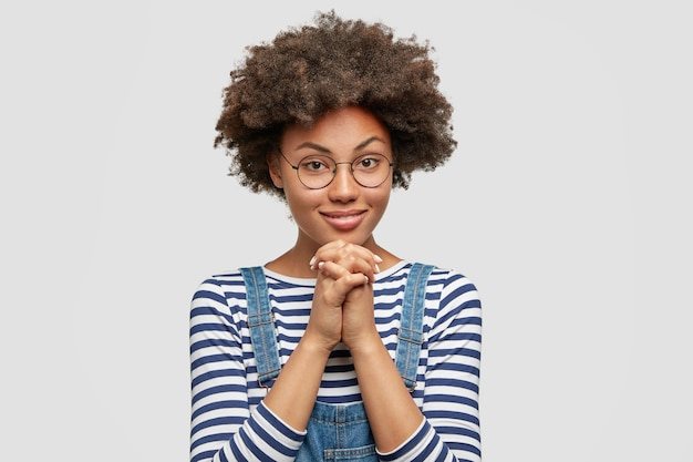 Jonge vrouw met afrokapsel die denimoveralls draagt