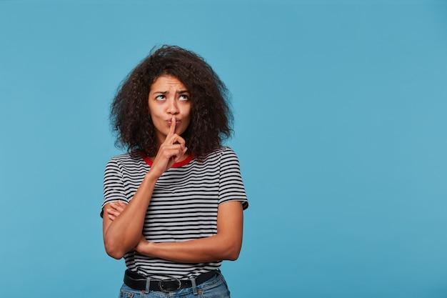 Jonge vrouw met afrokapsel die gestripte t-shirt over geïsoleerd dragen