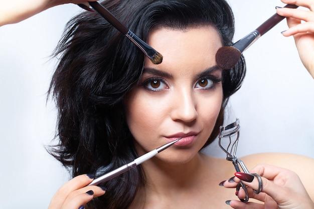 Jonge vrouw met allerlei make-up tools