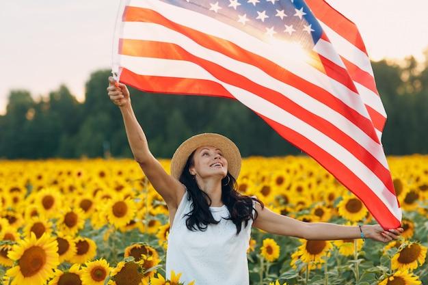 Jonge vrouw met amerikaanse vlag op het zonnebloemgebied