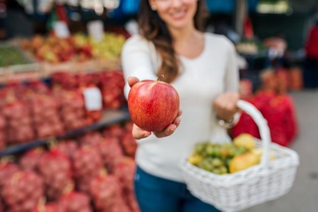 Jonge vrouw met appel in haar hand, aanbieden. focus op het fruit.