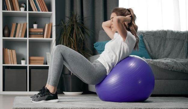 Jonge vrouw met armen achter hoofd achterover leunend op fitball tijdens trainingssessie in de woonkamer