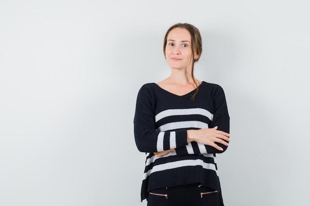 Jonge vrouw met armen gekruist in zwarte blouse en zwarte broek en op zoek gelukkig