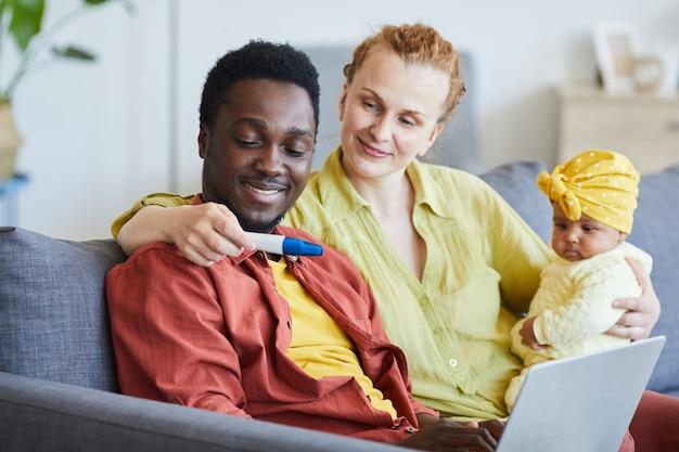 Jonge vrouw met baby op haar knieën die zwangerschapstest tonen aan haar echtgenoot terwijl zij thuis zitten