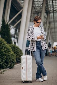 Jonge vrouw met bagage op luchthaven reizen en praten aan de telefoon