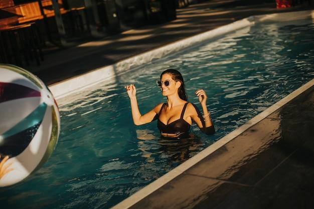 Jonge vrouw met bal in het zwembad