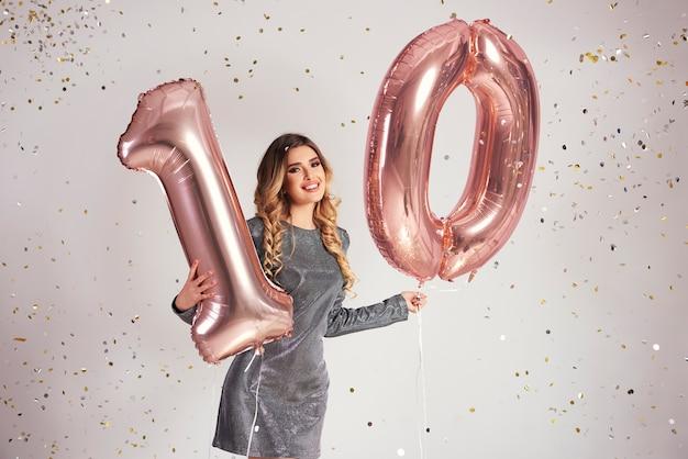 Jonge vrouw met ballonnen in vorm 10