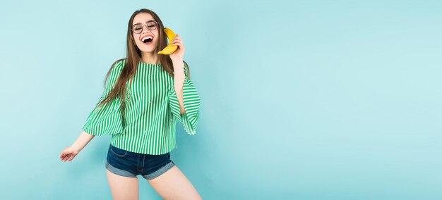Jonge vrouw met bananentelefoon