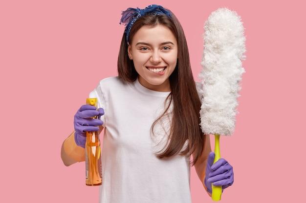Jonge vrouw met bandana op het hoofd die schoonmakende producten houden
