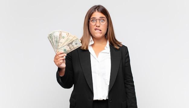 Jonge vrouw met bankbiljetten die verbaasd en verward kijkt, lip bijtend met een nerveus gebaar, het antwoord op het probleem niet weet