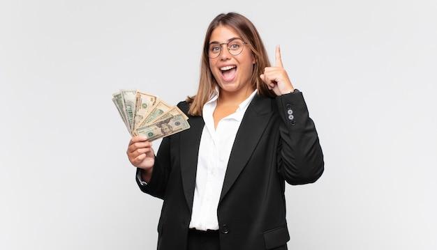 Jonge vrouw met bankbiljetten die zich als een gelukkig en opgewonden genie voelen na het realiseren van een idee, opgewekt vinger opsteken, eureka!