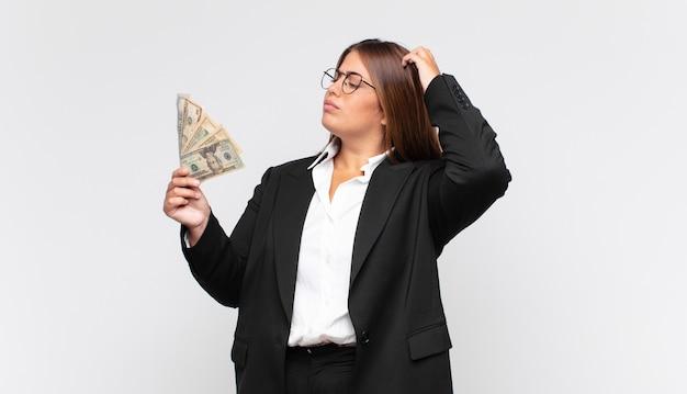 Jonge vrouw met bankbiljetten die zich in verwarring en verward voelen, hoofd krabben en naar de zijkant kijken
