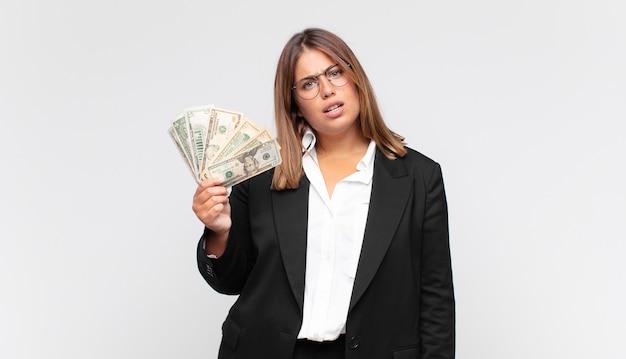 Jonge vrouw met bankbiljetten die zich verbaasd en verward voelen, met een domme, verbijsterde uitdrukking op zoek naar iets onverwachts