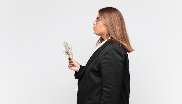 Jonge vrouw met bankbiljetten op profielweergave die ruimte vooruit wil kopiëren, denken, fantaseren of dagdromen