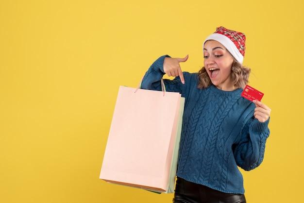 Jonge vrouw met bankkaart en pakketten na het winkelen op geel