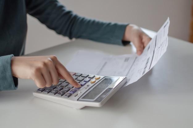 Jonge vrouw met behulp van calculator voor analyse en het berekenen van familie budget kosten rekeningen rapport over bureau in kantoor aan huis