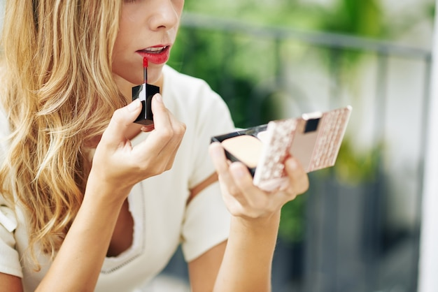 Jonge vrouw met behulp van compacte spiegel bij het aanbrengen van rode vloeibare lippenstift na het eten van lunch in café