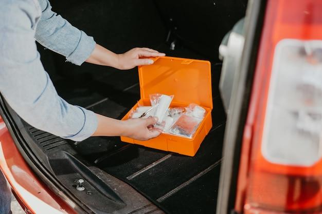 Jonge vrouw met behulp van de doos van de auto-ehbo-kit met een soort medische hulpmiddelen, transportconcept
