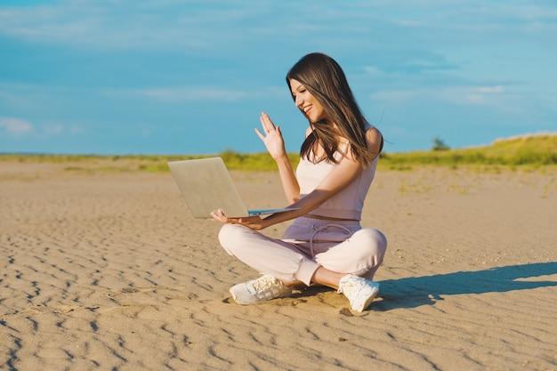 Jonge vrouw met behulp van de laptop op het strand