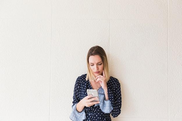 Jonge vrouw met behulp van de mobiele telefoon voor muur