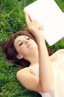 Jonge vrouw met behulp van digitale tablet op weide