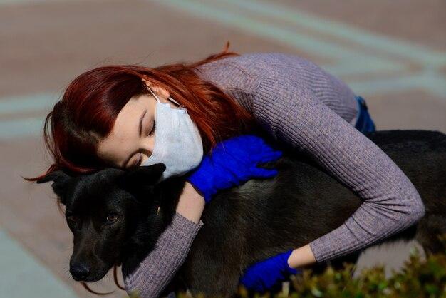 Jonge vrouw met behulp van een gezichtsmasker en haar hond knuffelen.
