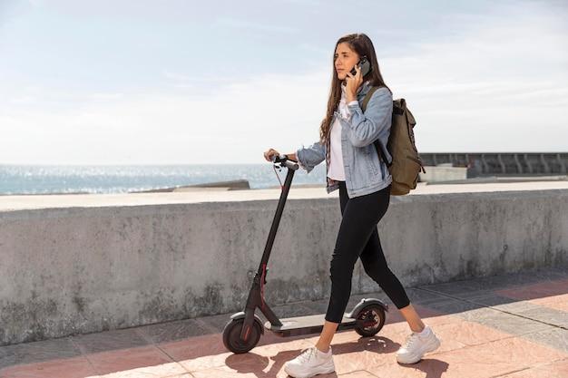 Jonge vrouw met behulp van een scooter buitenshuis