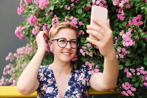 Jonge vrouw met behulp van een smartphone in de buurt van een bloemstruik