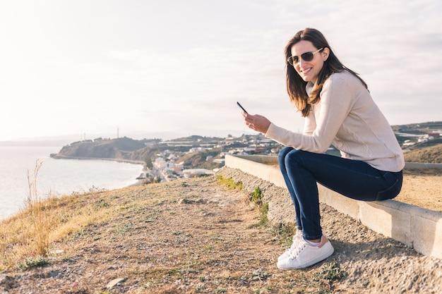Jonge vrouw met behulp van haar mobiele telefoon in de voorkant van de zee in het voorjaar