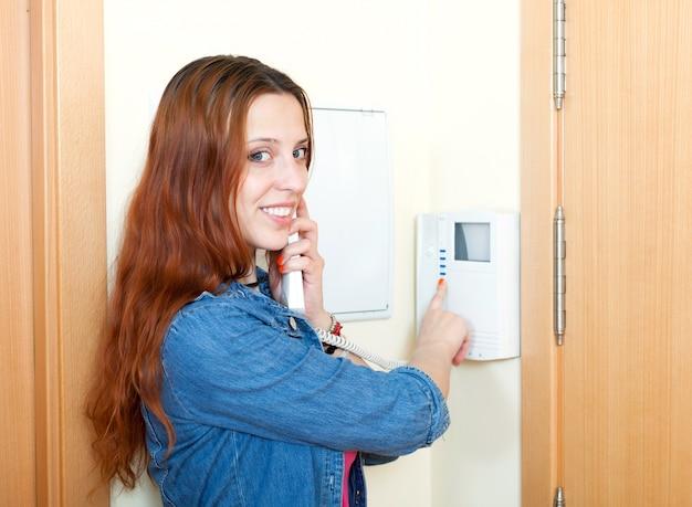 Jonge vrouw met behulp van huis videofoon binnen