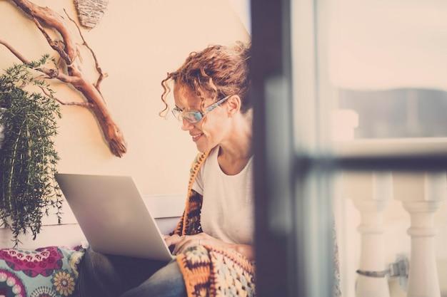 Jonge vrouw met behulp van laptop en werken zittend op het terras. tevreden vrouw die werkt of studeert op een laptop op het huisterras. gelukkige jonge vrouw die op internet of sociale media-apps op laptop surft