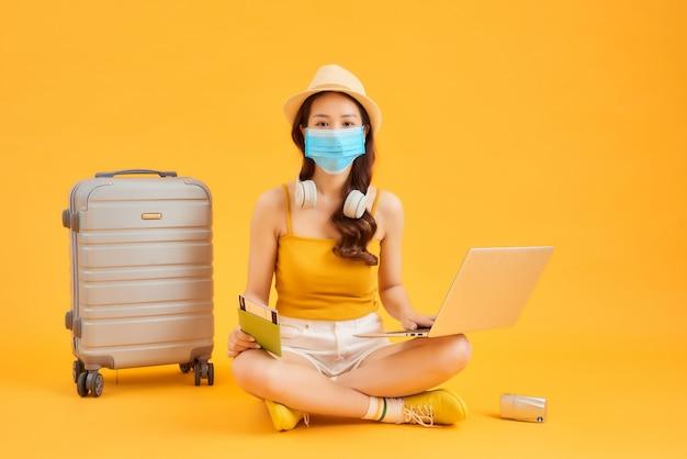 Jonge vrouw met behulp van laptop, gezichtsmasker dragen