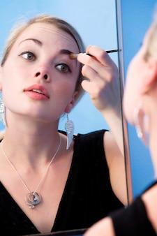 Jonge vrouw met behulp van make-up borstel