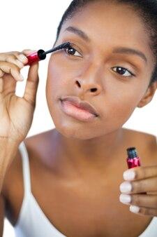 Jonge vrouw met behulp van mascara voor haar wimpers
