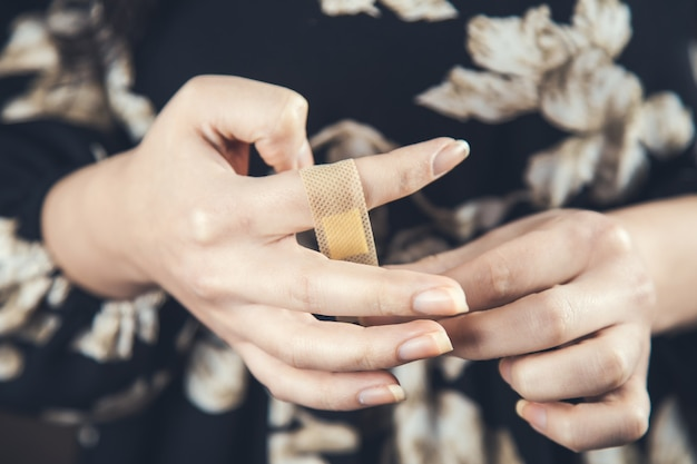 Jonge vrouw met behulp van medische pleister op vinger