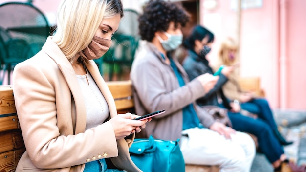 Jonge vrouw met behulp van mobiele slimme telefoon gedekt door gezichtsmasker op covid derde golf