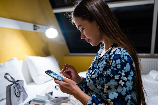 Jonge vrouw met behulp van mobiele smartphone. gelukkig lachend mooi meisje op bed in slaapkamer typen op mobiele smartphone