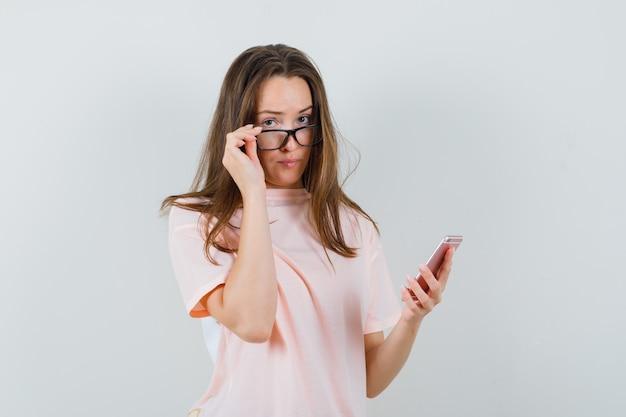 Jonge vrouw met behulp van mobiele telefoon, bril opstijgen in roze t-shirt, vooraanzicht.