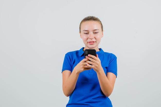 Jonge vrouw met behulp van mobiele telefoon en lachend in blauw t-shirt