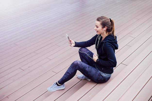 Jonge vrouw met behulp van mobiele telefoon en sittinng op trappen