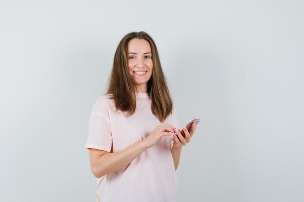 Jonge vrouw met behulp van mobiele telefoon in roze t-shirt en op zoek blij. vooraanzicht.