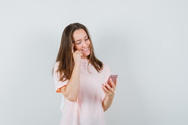 Jonge vrouw met behulp van mobiele telefoon in roze t-shirt en vrolijk, vooraanzicht op zoek.