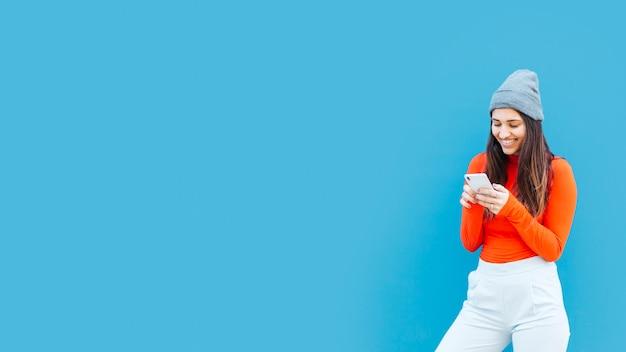 Jonge vrouw met behulp van mobiele telefoon op blauwe achtergrond met kopie ruimte