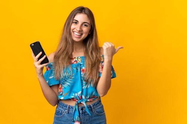 Jonge vrouw met behulp van mobiele telefoon op geïsoleerd geel wijzend naar de zijkant om een product te presenteren
