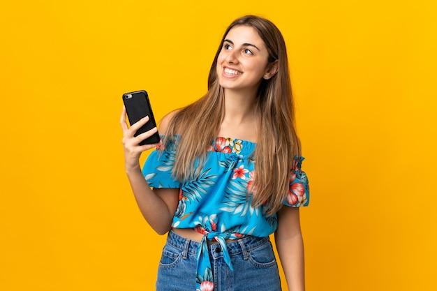 Jonge vrouw met behulp van mobiele telefoon op geïsoleerde geel opzoeken tijdens het glimlachen