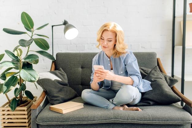 Jonge vrouw met behulp van mobiele telefoon op gezellige zwarte bank, woonkamer in witte tinten en pot met bloem