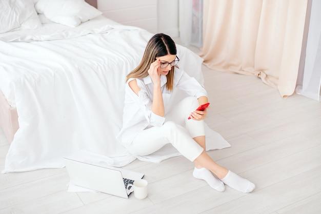 Jonge vrouw met behulp van mobiele telefoon zittend in de buurt van bed thuis met laptop en koffiekopje